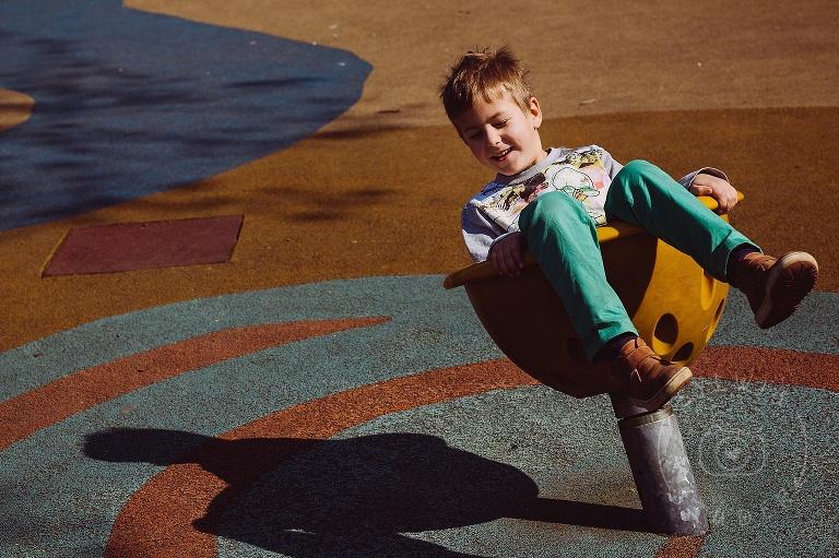 zdjęcia chłopca na placu zabaw w popołudniowym słońcu