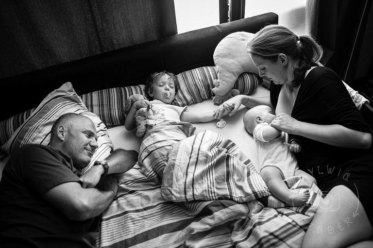 rodzinny portret mama tata i dzieci zasypiają w łóżku rodziców