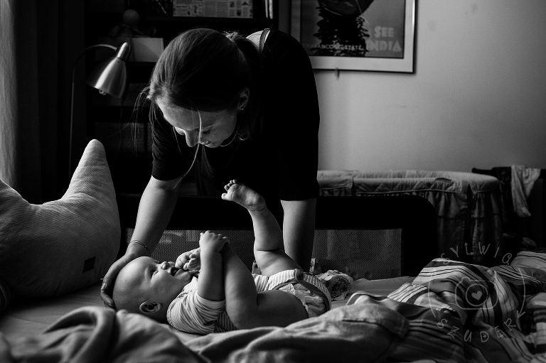 portret mamy z niemowlakiem w łóżku rodziców