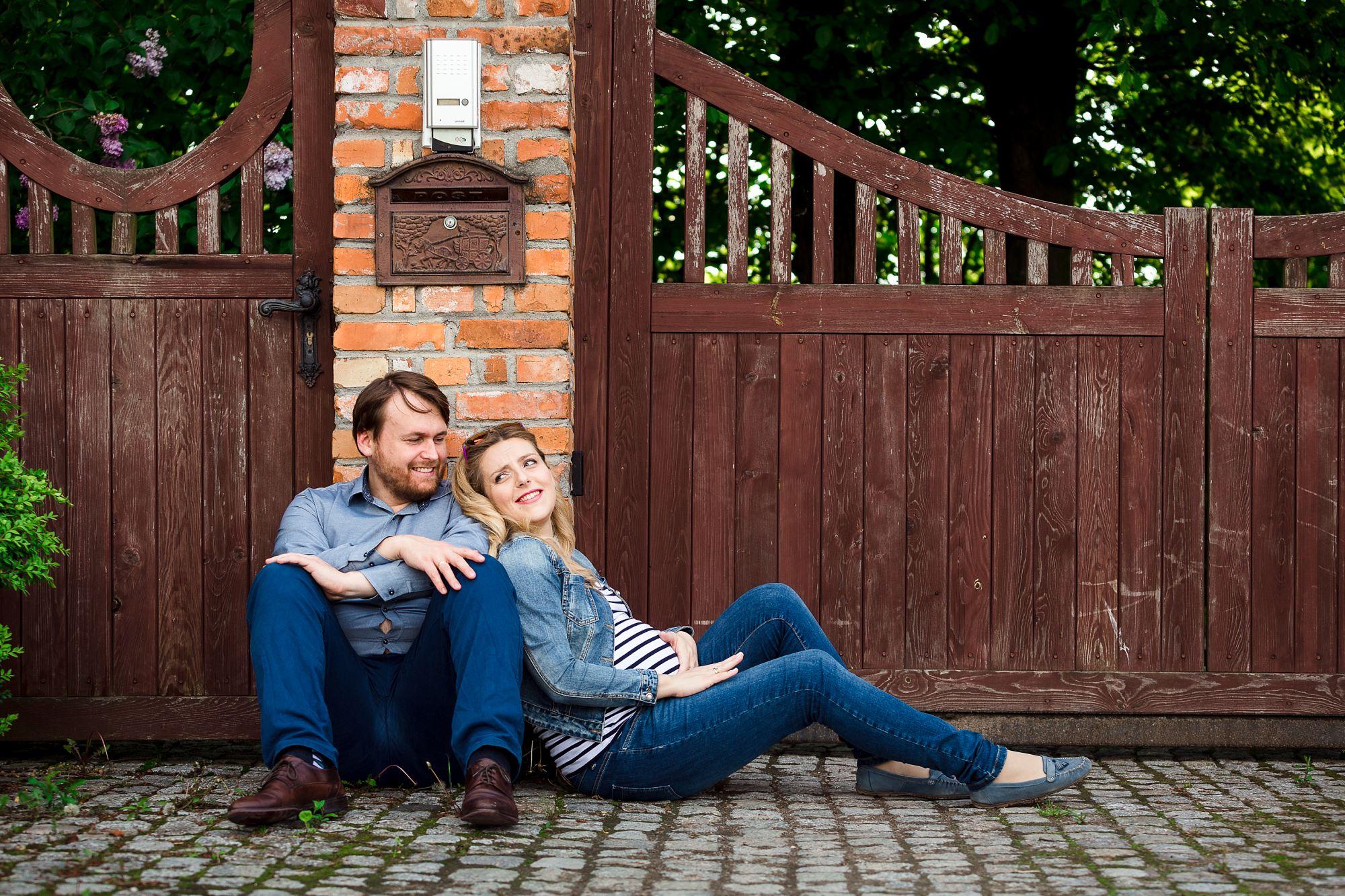 kobieta w ciąży siedzi na ziemi i opiera się o swojego męża