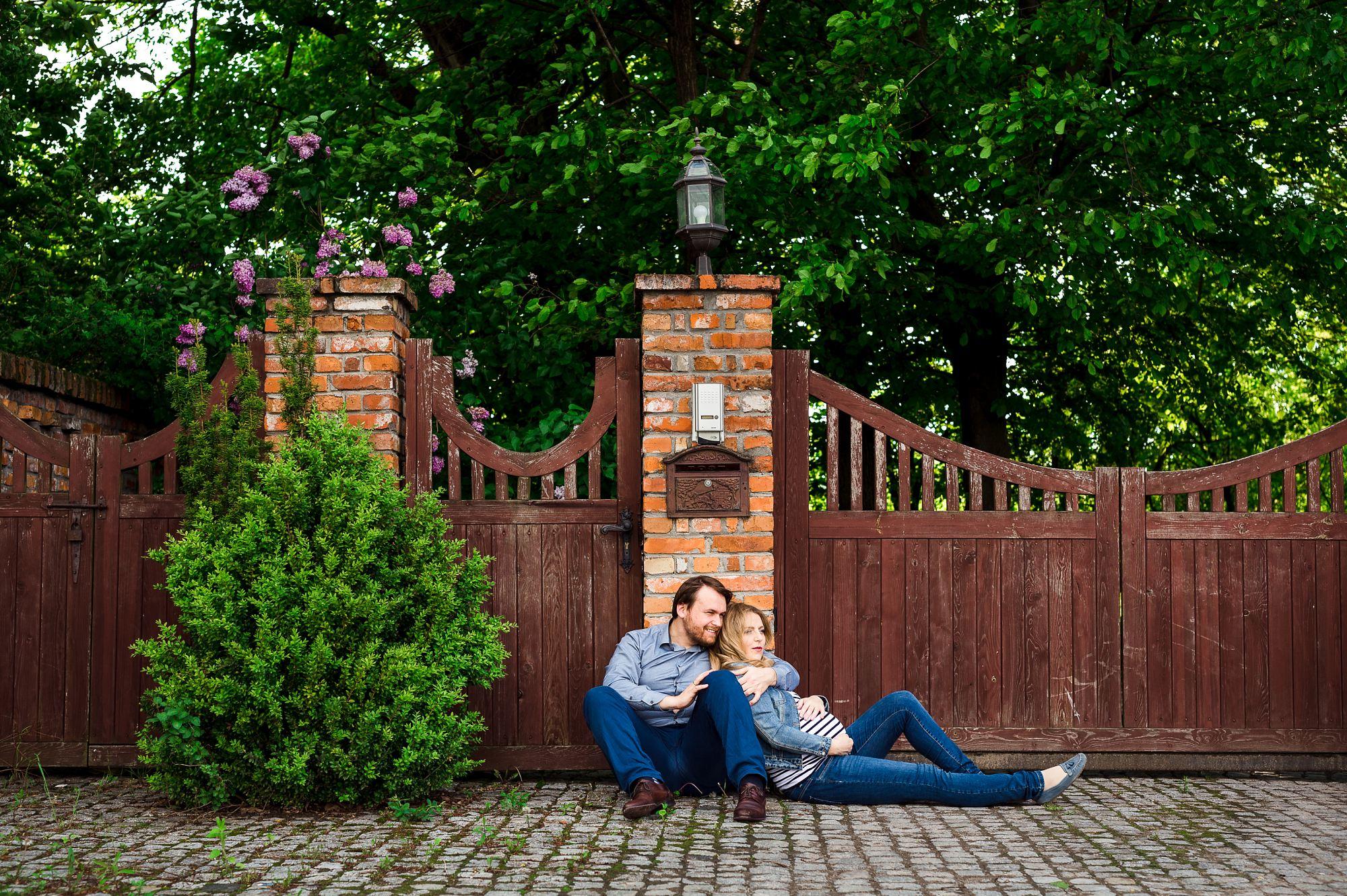 para przyszłych rodziców siedzi pod starą bramą i murem z cegieł w Starych Babicach