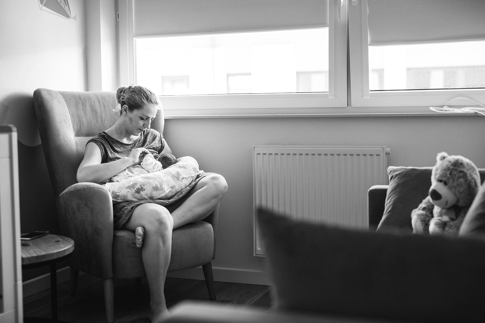 kobieta siedzi w fotelu i karmi piersią swoje kilkudniowe dziecko