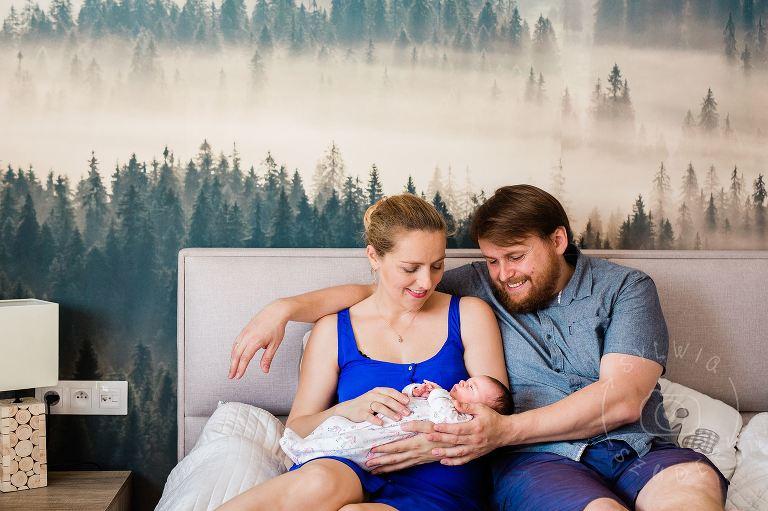 świeżo upieczona para rodziców spogląda z czułością na noworodka